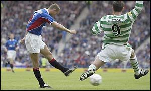 Lovenkrands takes on Chris Sutton during an Old Firm Game