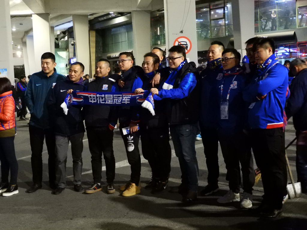 """Supporters took group photos with a scarf writing: """" Shenhua is the Champion""""."""